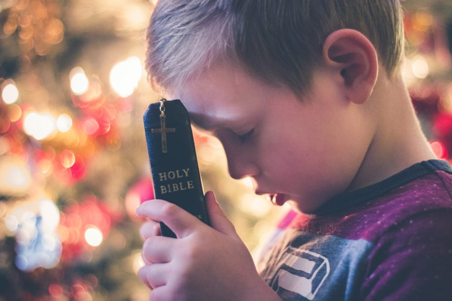 little boy with head bowed over a Bible