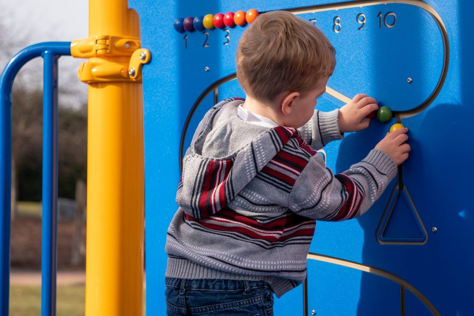 little boy playing with outside activity wall