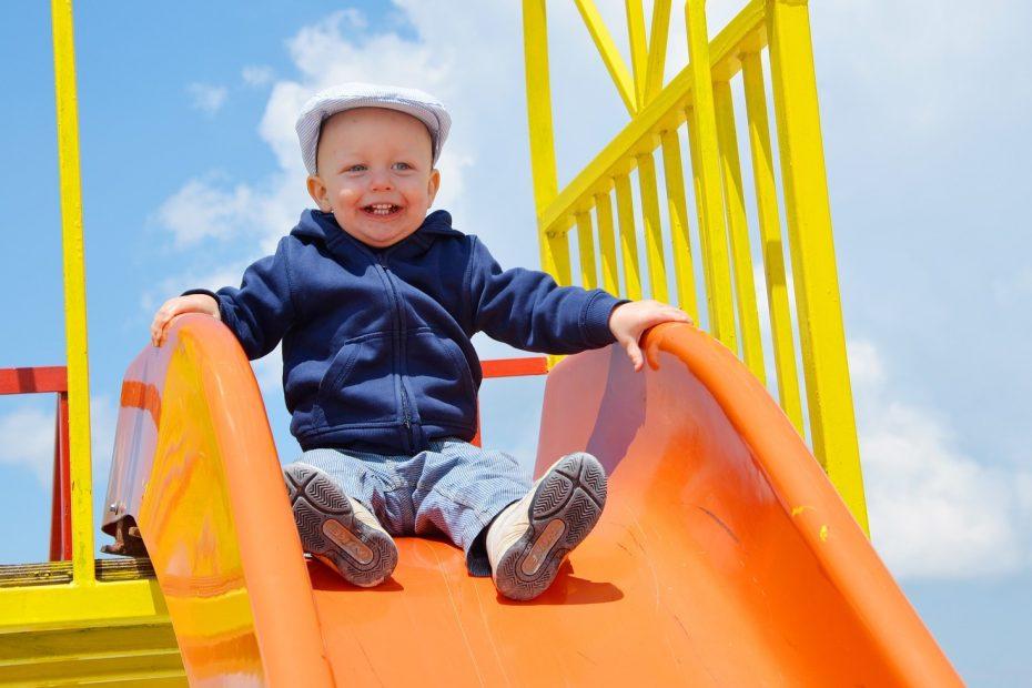 little boy on top of a slide