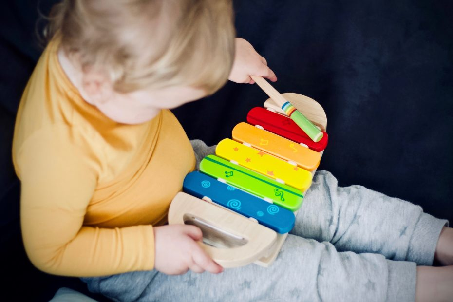small child playing with xylophone